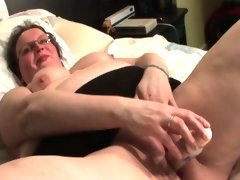 Aroused mature masturbating with sex toy